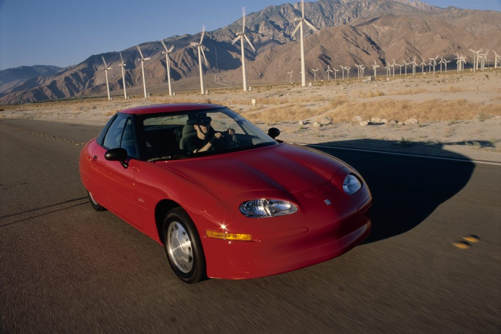 A red GM EV1 parked on a road alongside wind turbines and mountains