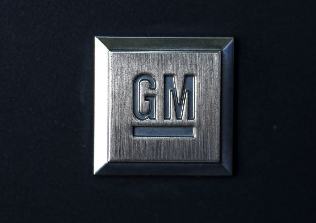 A charcoal grey plaque with the General Motors logo, GM, on it against a black background.