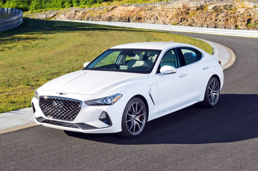 A white Genesis G70 luxury sedan model driving on a country highway