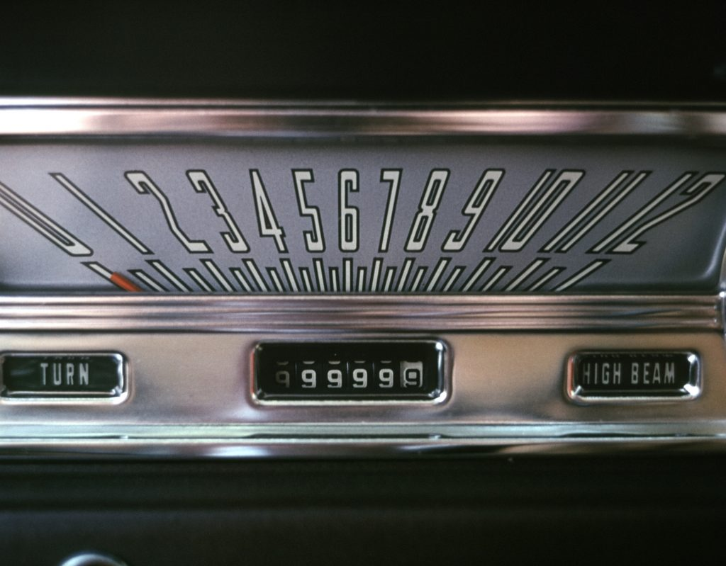 A vintage car with an odometer reading all 9s.
