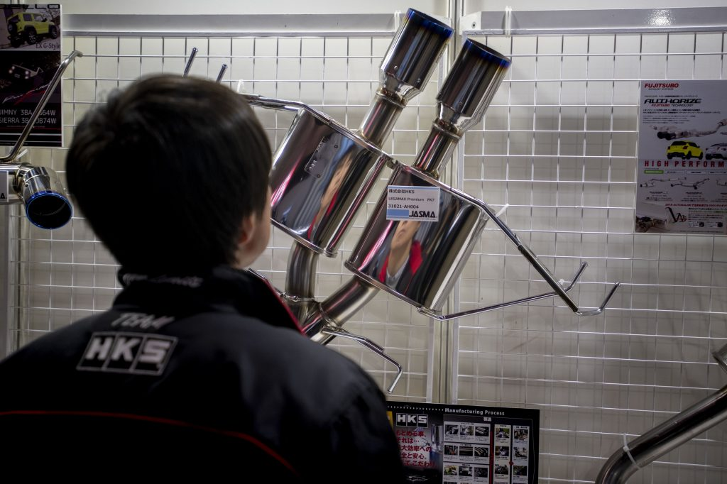 A man stares at an aftermarket exhaust system on display