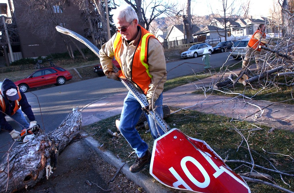 Downed stop sign being collected by a worker