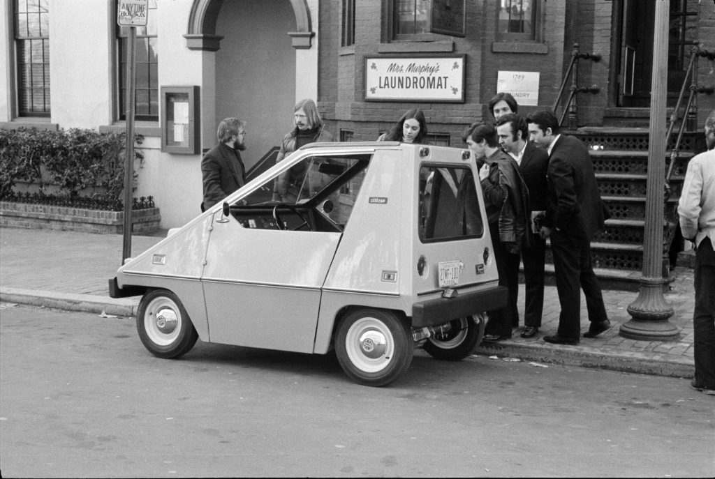 People standing around Sebring-Vanguard CitiCar parked on side of the road.