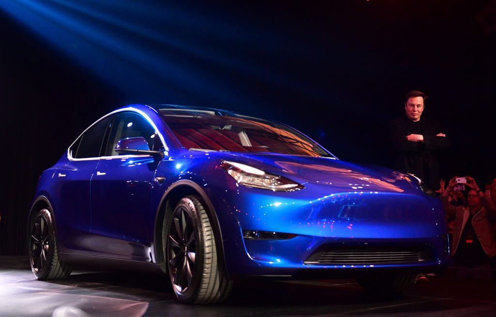 Tesla CEO Elon Musk stands next to a blue Tesla Model Y SUV.