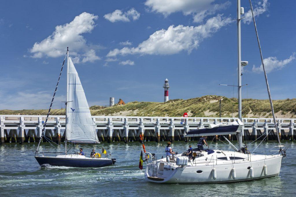 Sailboats and yachts sailing past wooden docks.