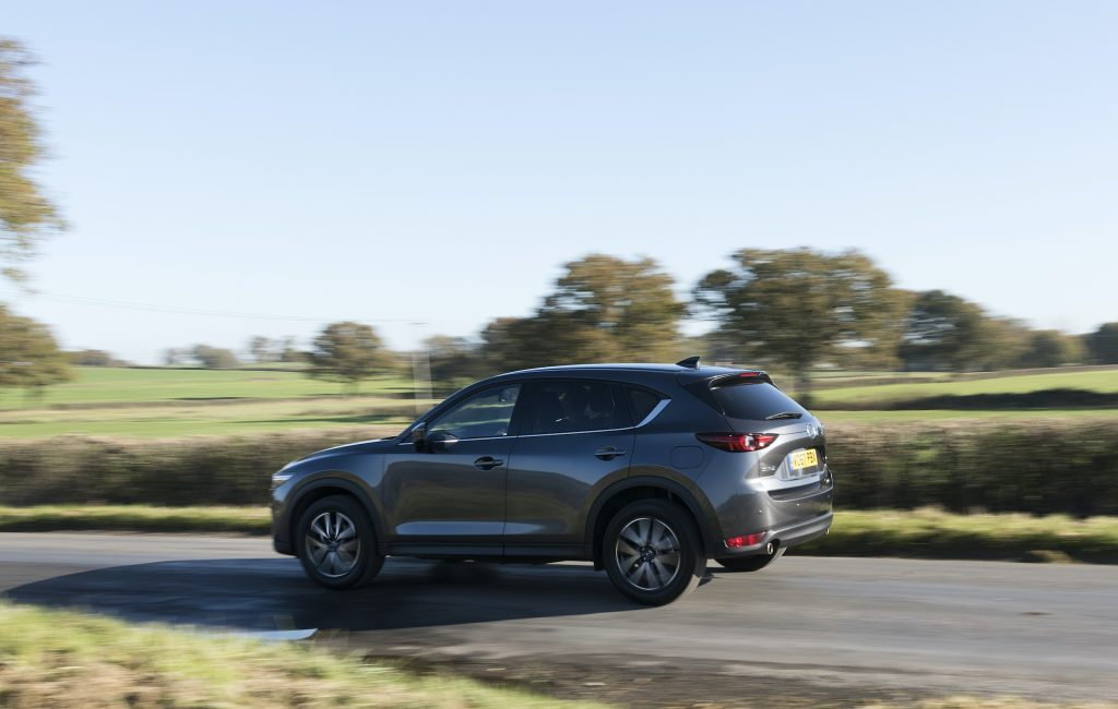 The second generation Mazda CX-5 driving at speed on a scenic country road.