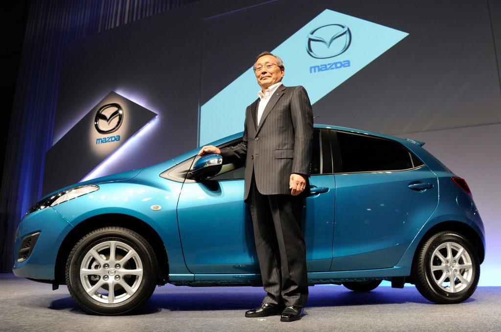 a blue 2011 Mazda Mazda3 hatchback alongside the Mazda president at a press conference.