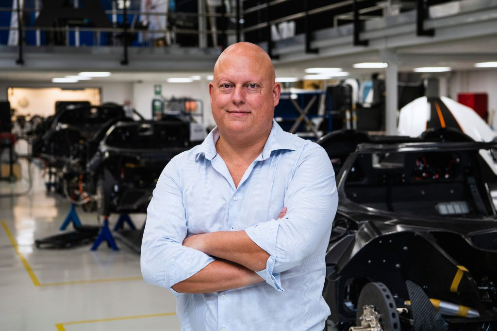 Christian von Koenigsegg stands with arms folded at his factory. with partially assembled cars in the background
