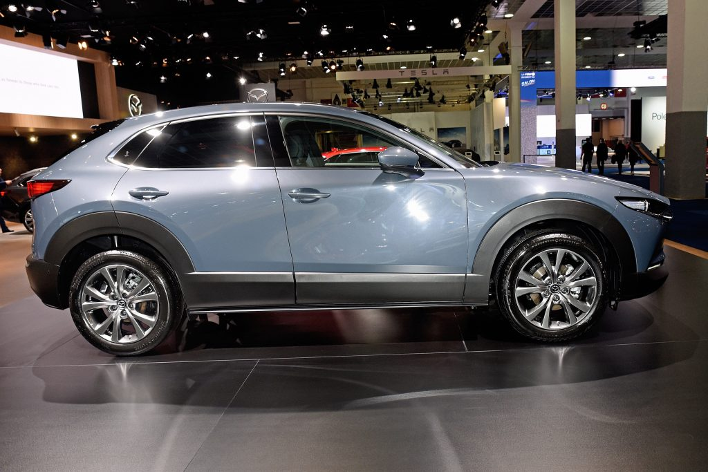 a side view of a light blue 2021 Mazda CX-30 on display at an indoor auto show