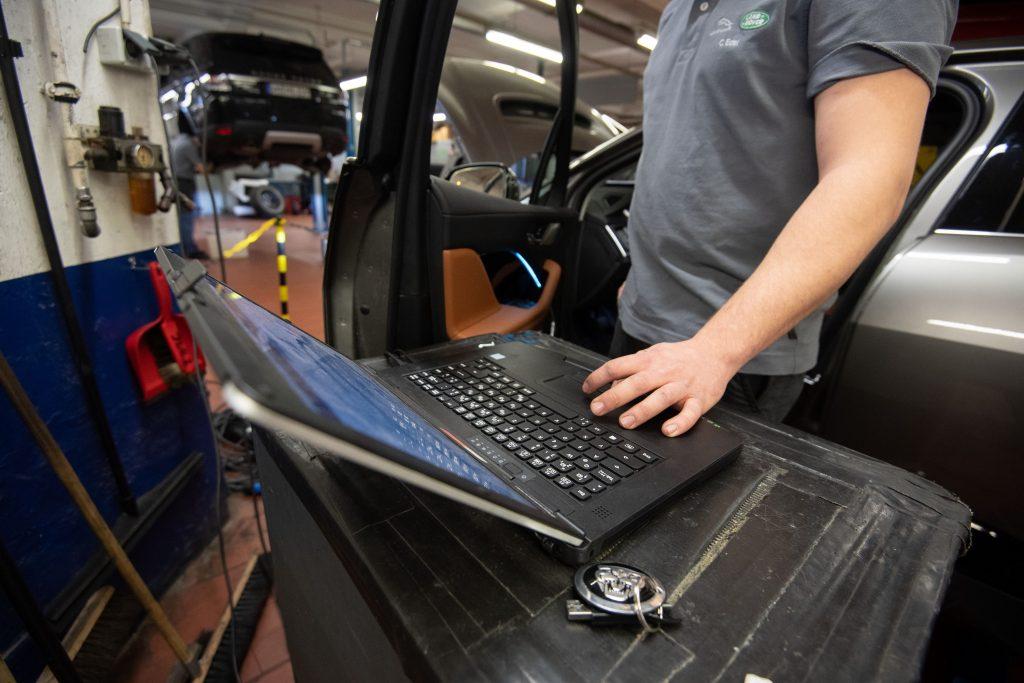 A mechanic uses a laptop to work on a Jaguar