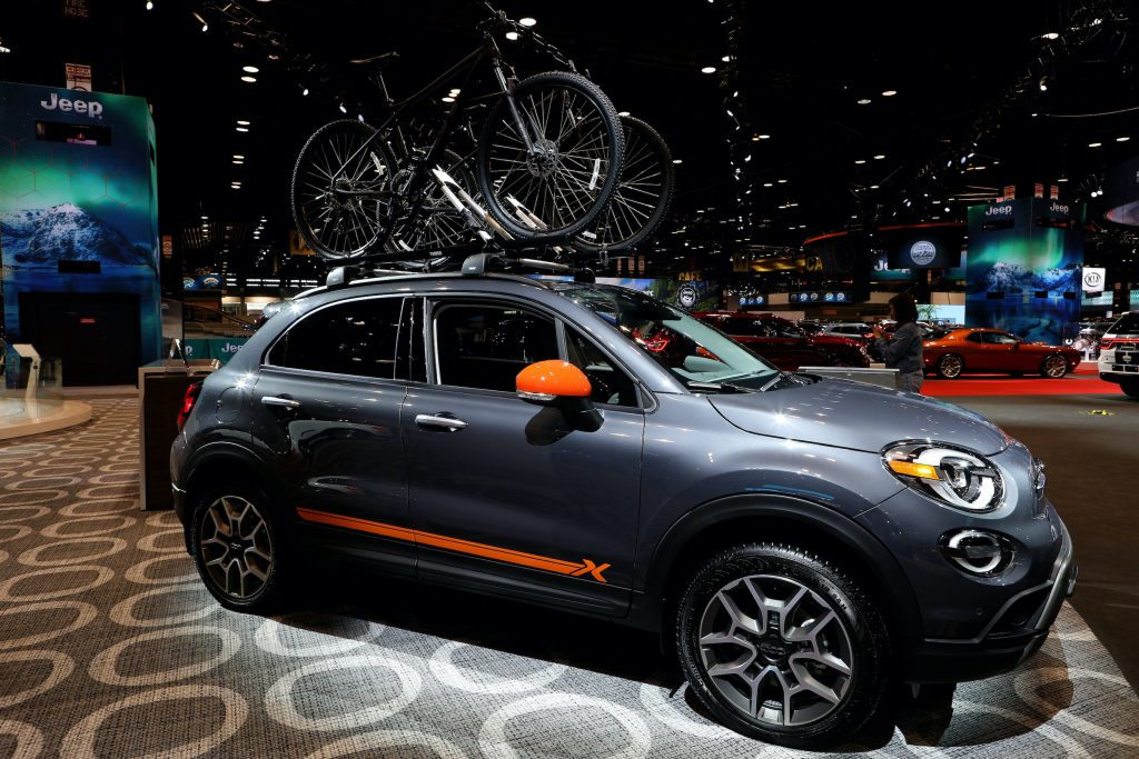 a Fiat 500 X on display with bicycles on top