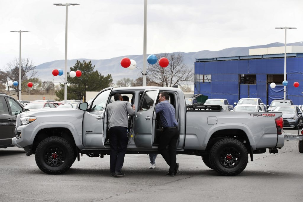 A group of men crowd around a new Tacoma on a dealership lot