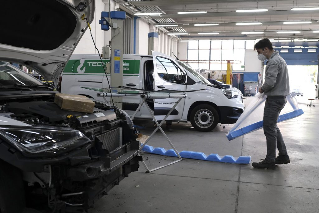 A mechanic works in an auto body shop in Italy