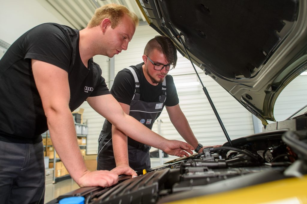 Two mechanics peer into the engine bay of a car in for repairs