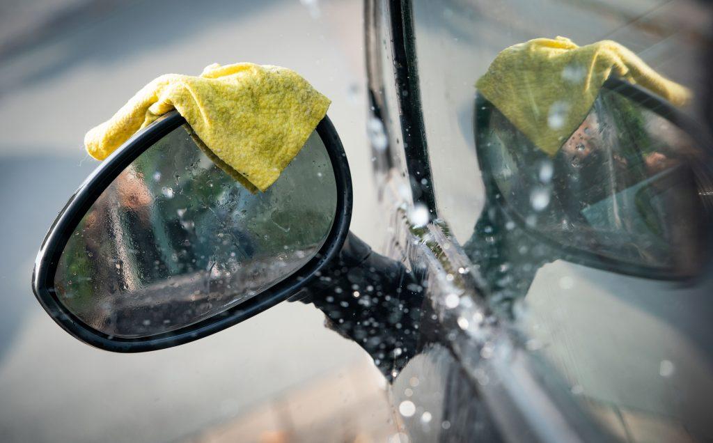 A rag lies on the rear-view mirror of a car during a car wash.