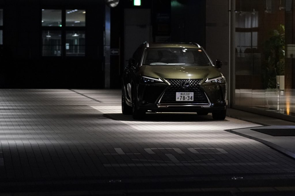 2021 Lexus UX250 parked in the dark on a gray brick paved street