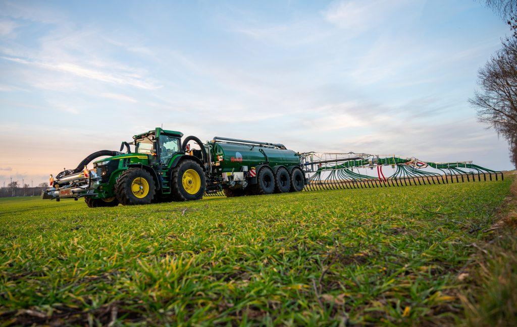A farmer spreads liquid manure on a field with his team in a giant John Deere tractor farming machine