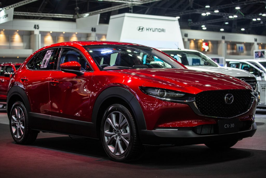 a red 2021 Mazda CX-30 on display at an indoor auto show, front quarter view