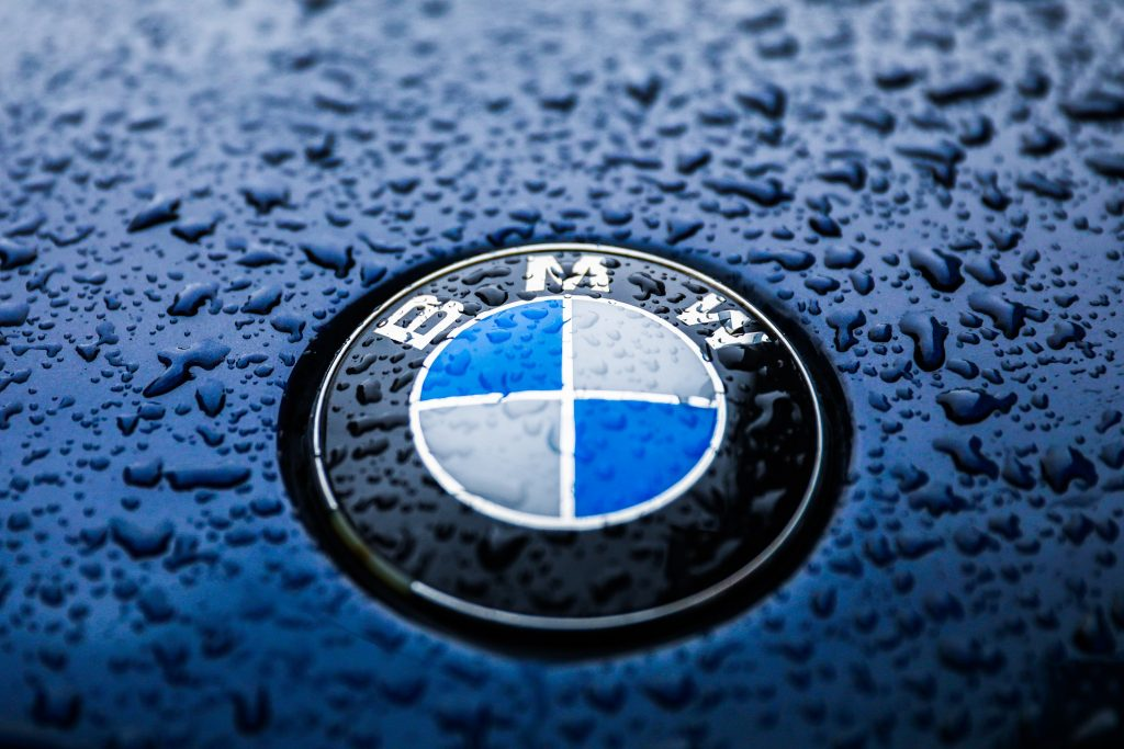 BMW's logo on the hood of one of their vehicles, wet from the rain.
