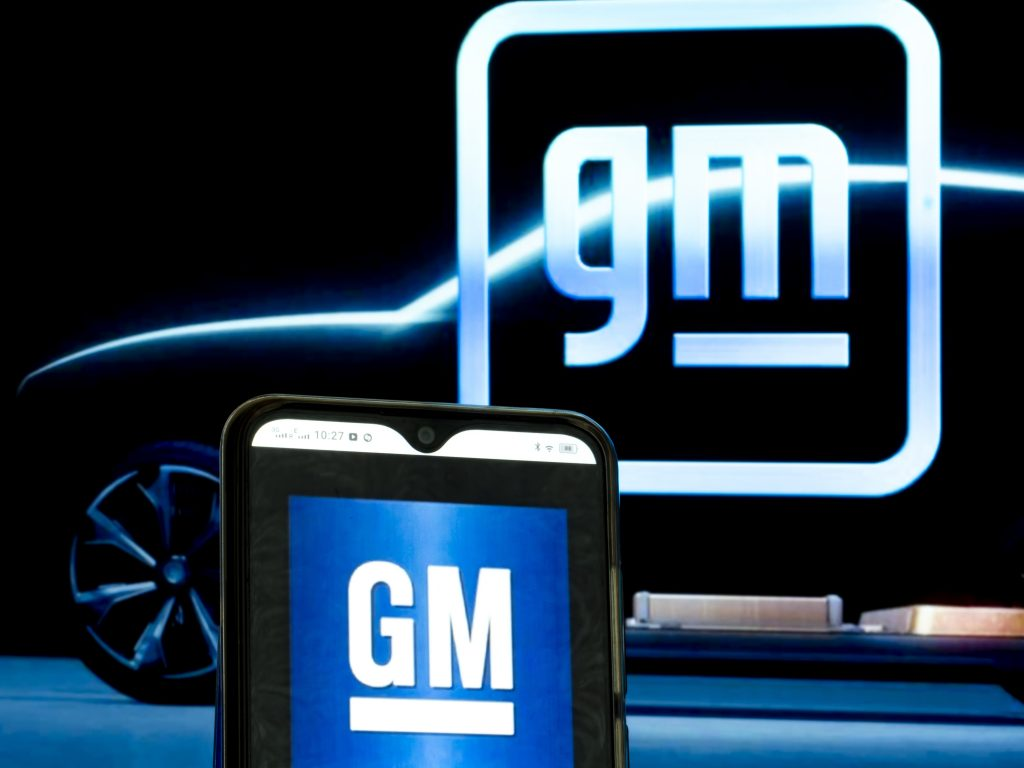 The old and new GM logos illuminated against a black backdrop