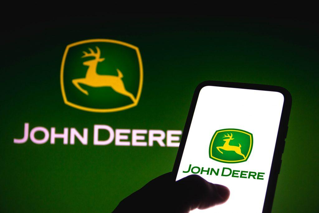 a John Deere logo on a smart phone against a green backdrop that also sports the John Deere logo