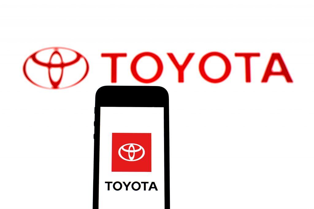 Toyota Motor Corporation logo on a white screen with a phone that also has the logo pulled up