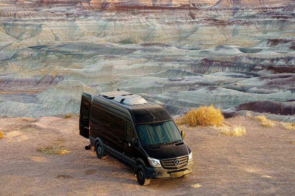 A black Mercedes-Benz Sprinter camper sits in the desert at sunset