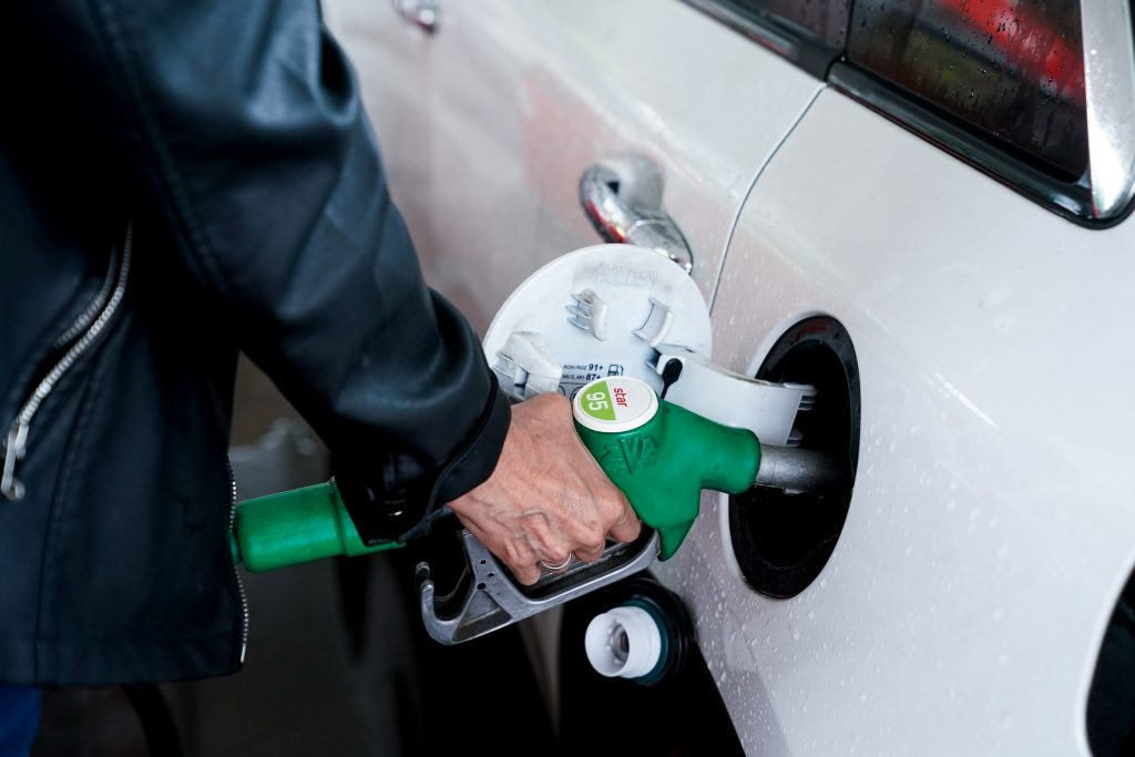 A woman pumps gas into her white car in Madrid