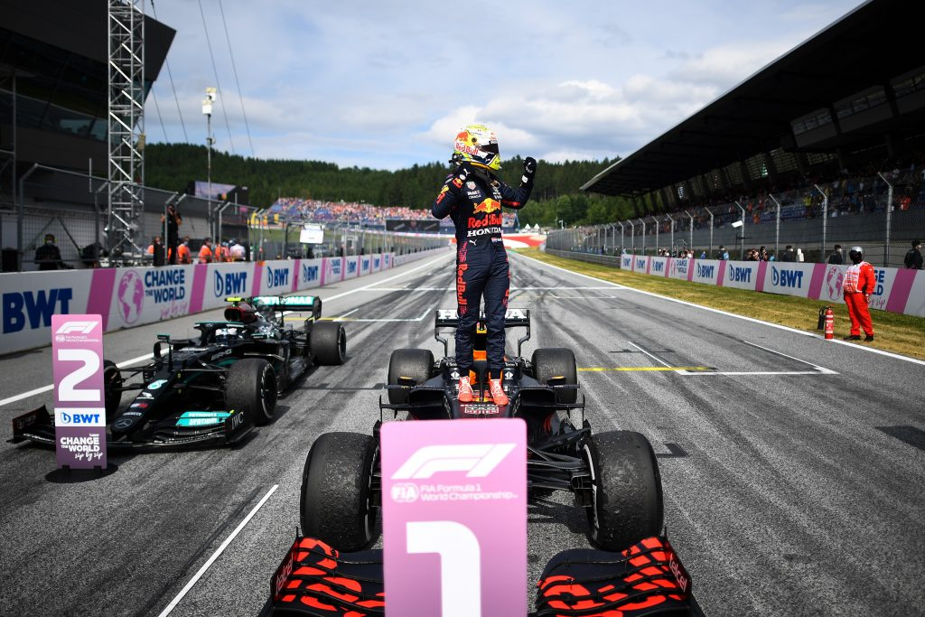Max Verstappen stands, hands raised, on the top of his F1 car after winning the Austrian Grand Prix
