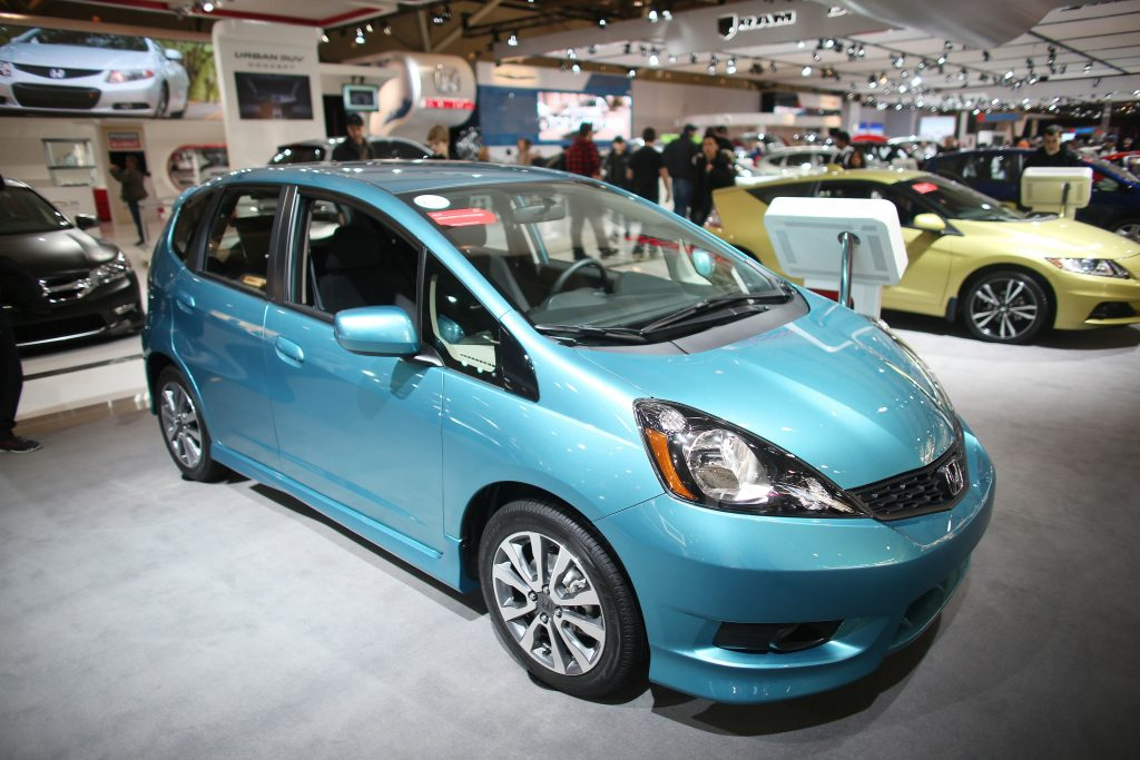 A teal blue Honda fit in the booth at an auto show
