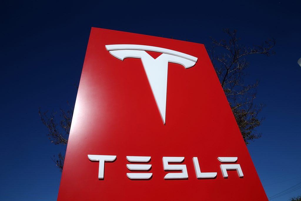 """A red sign featuring white font that reads """"Tesla"""" with the brand's logo across the top"""