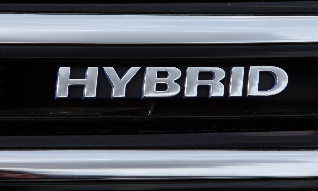 A silver Hybrid Electric Vehicle (HEV) badge