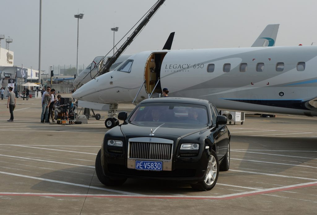 A black Rolls Royce in front of a private jet
