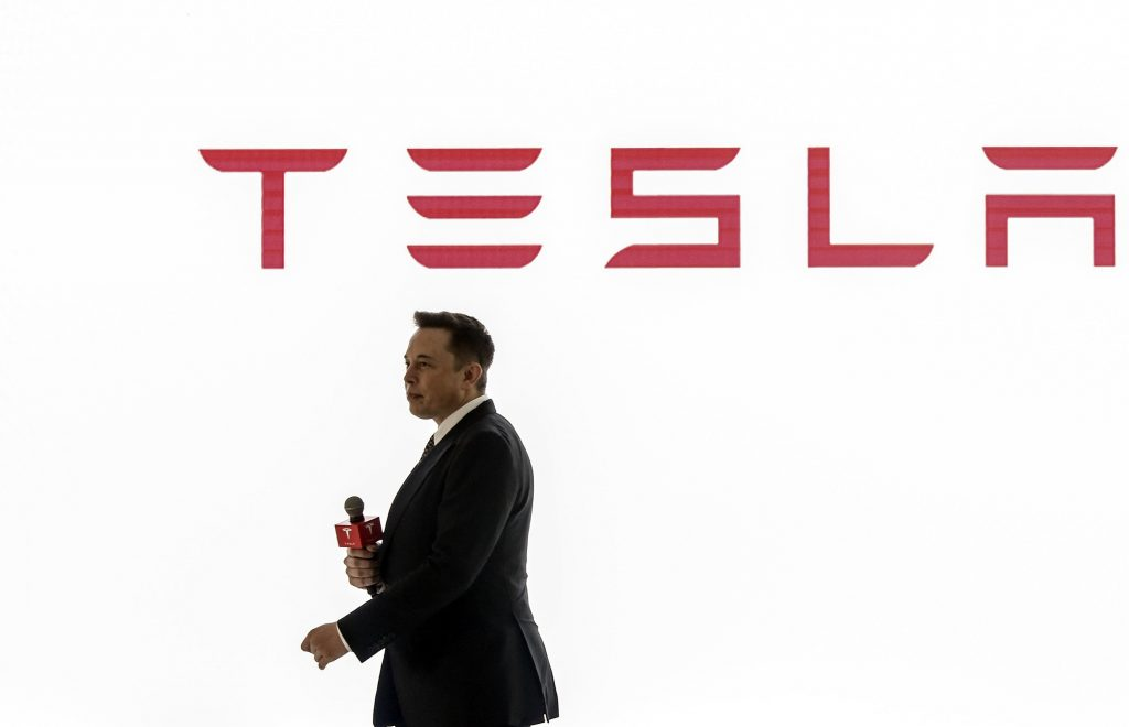 Tesla CEO Elon Musk presents at a conference with the brand's logo seen in red on a white background behind him