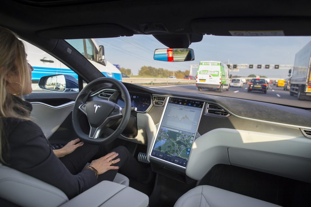 A woman sits in a Tesla with her hands off the while as the vehicle pilots itself.