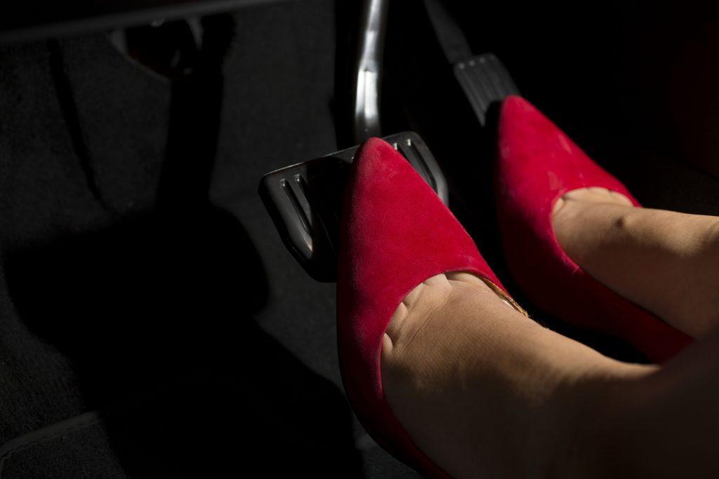 A woman wearing red heels demonstrates left foot braking