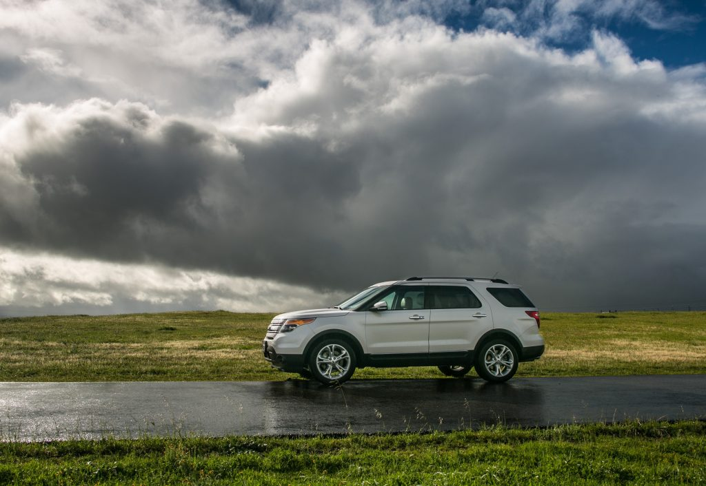 A white Ford Escape SUV on a road wet from recent rain