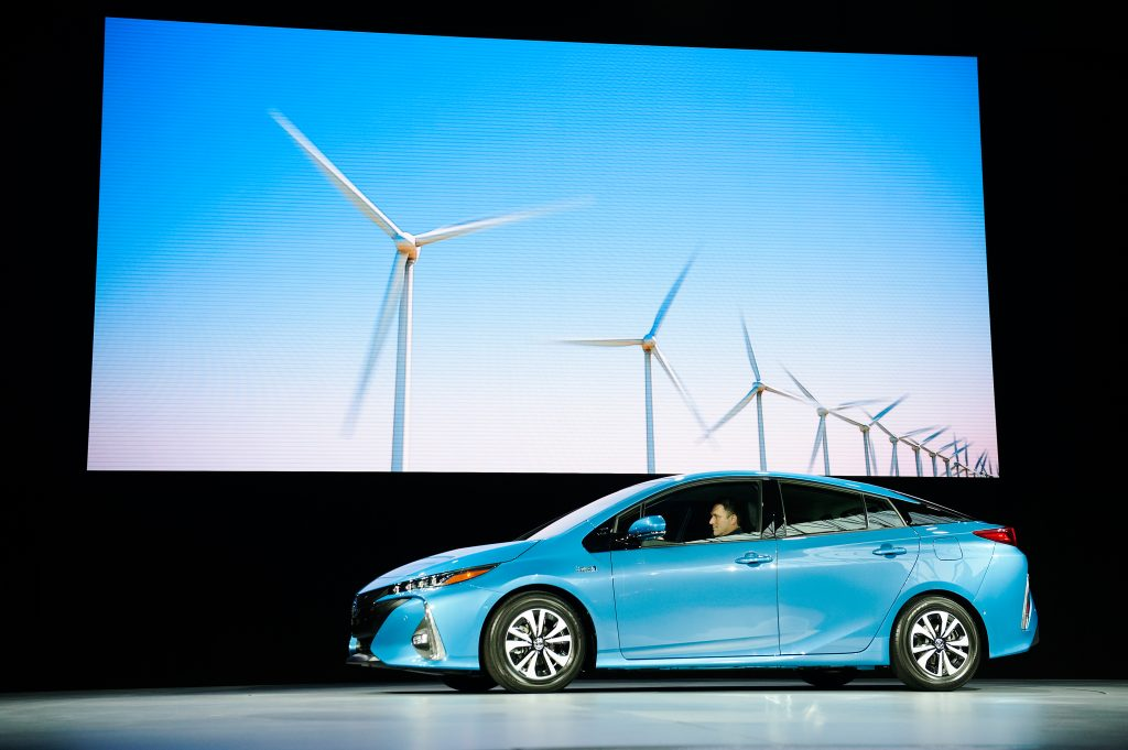 A bright blue hybrid Prius Prime posing in front of a windmill graphic