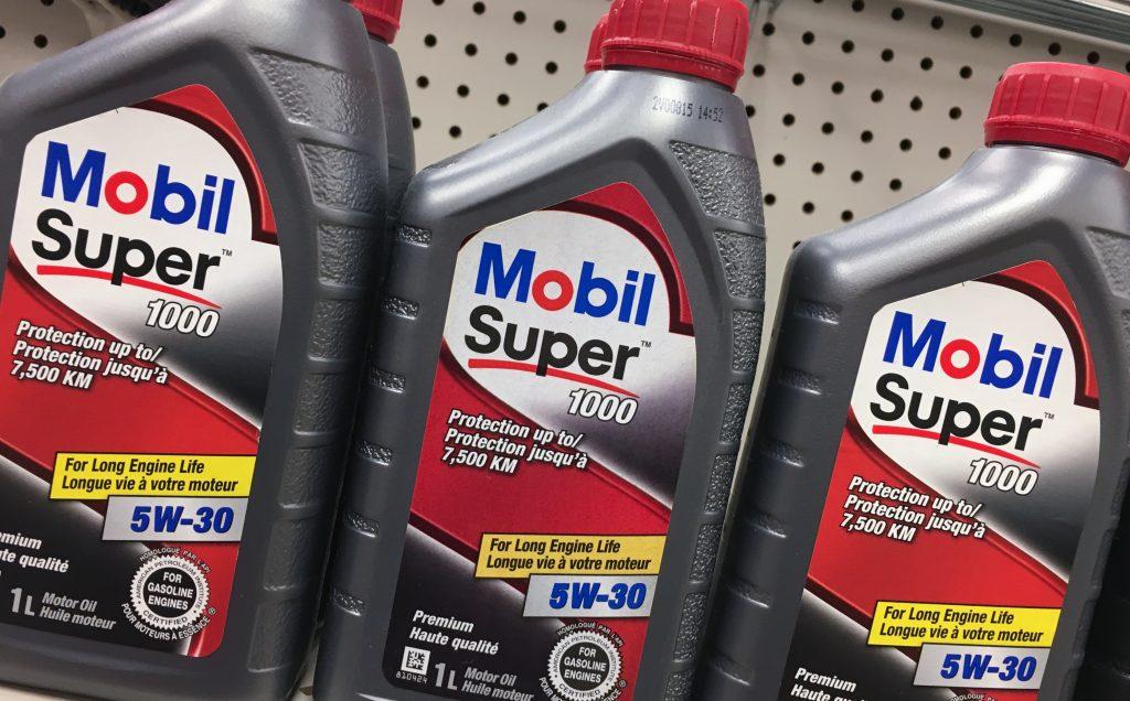 Mobil Super motor oil bottles on a hardware store shelf.