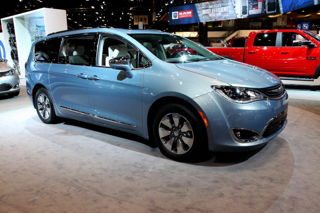 a blue Chrysler Pacifica minivan on display at an indoor auto show