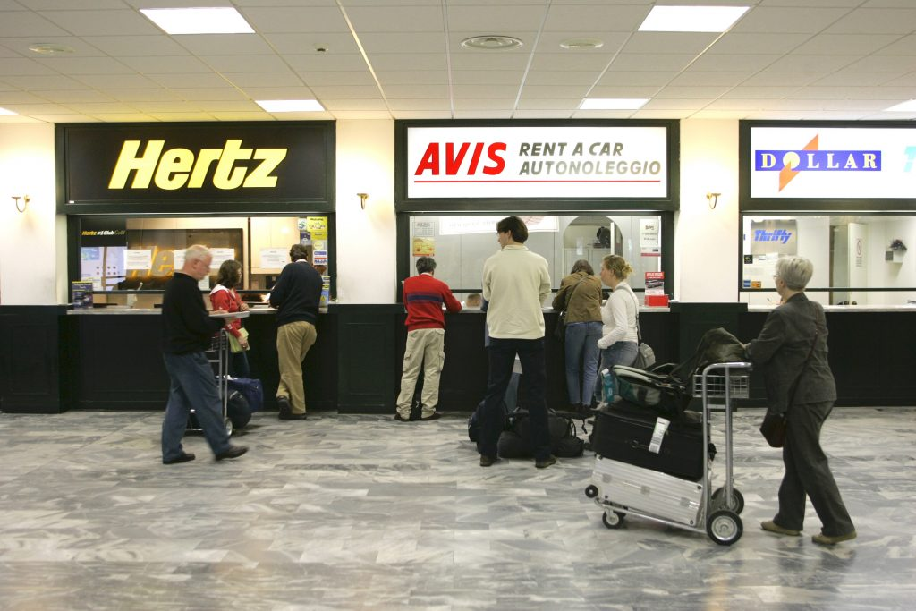 A rental car desk, shown with agents filling out paperwork and selling rental car insurance