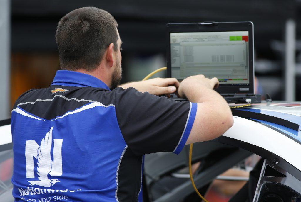 A NASCAR pit mechanic works on a laptop