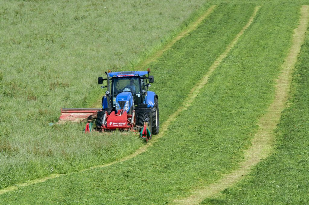 a new holland tractor cutting a hay field