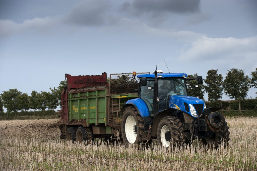 a new holland tractor spreading manure in an agricultural field