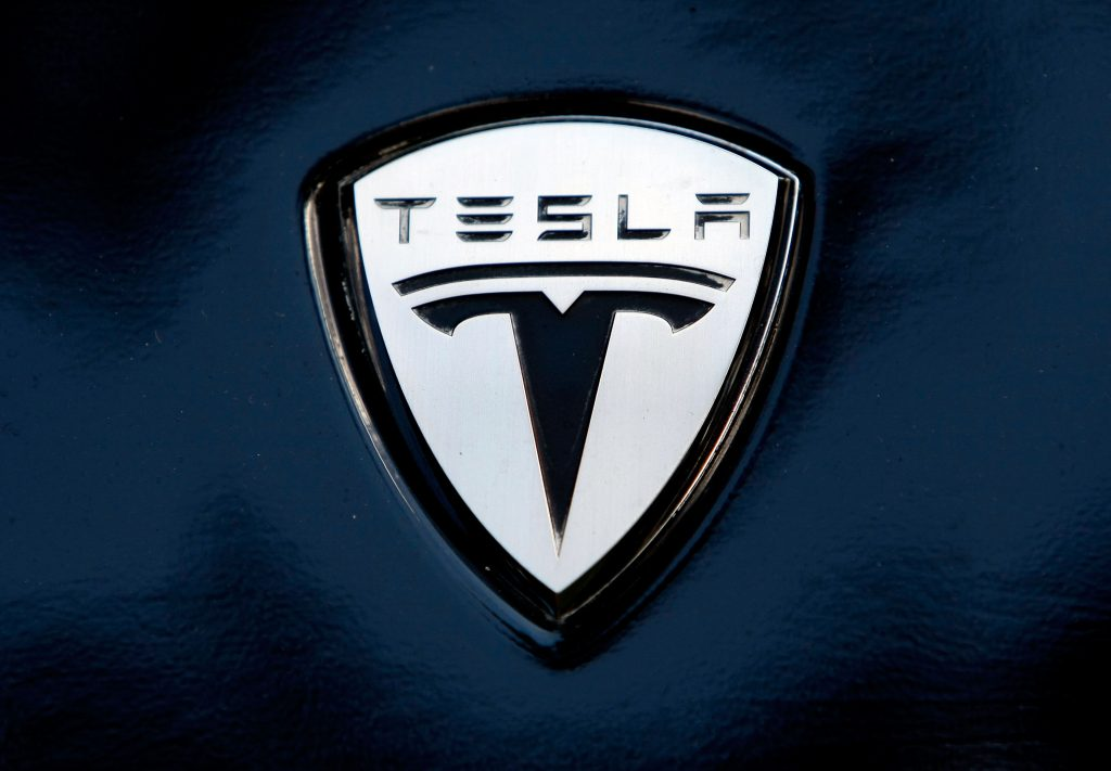 Tesla's logo seen on the fender of one of their models, painted dark blue
