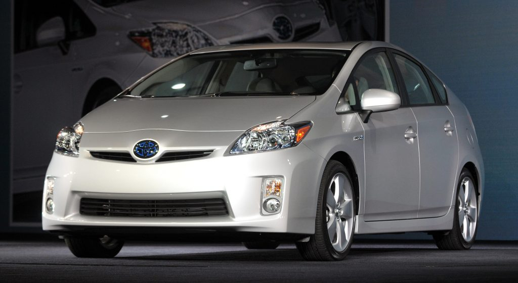 a silver 2010 Toyota Prius on display at an indoor auto show.