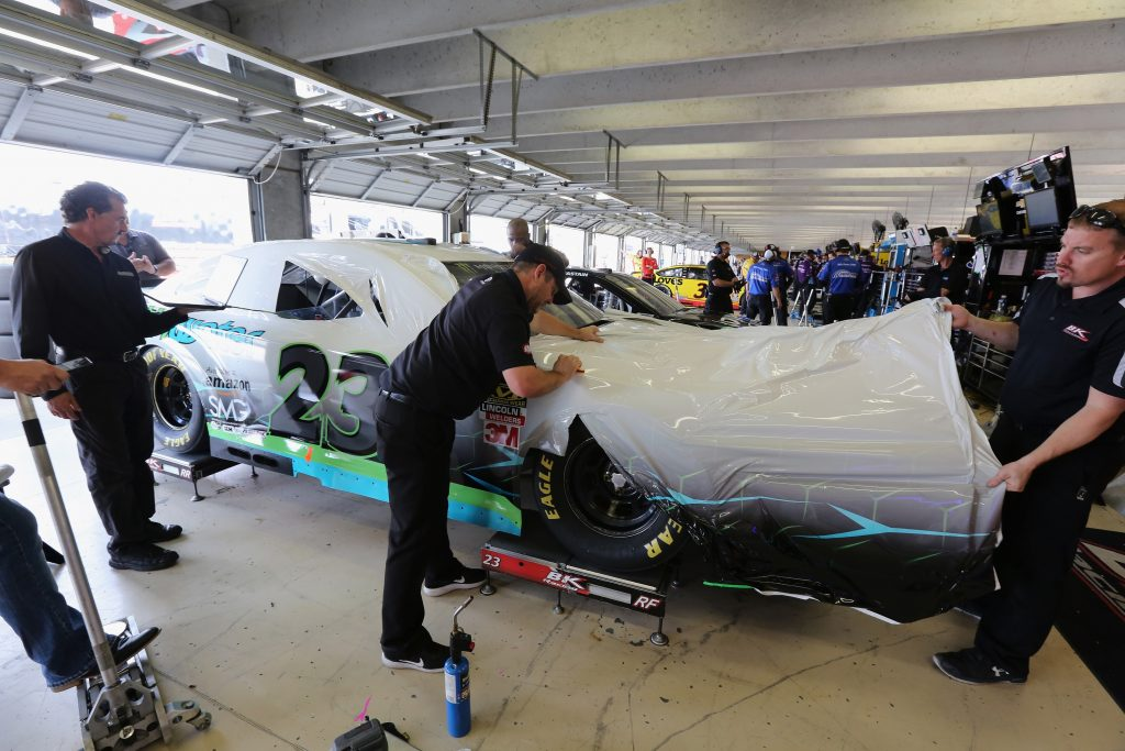 NASCAR team members apply a car wrap to one of their vehicles