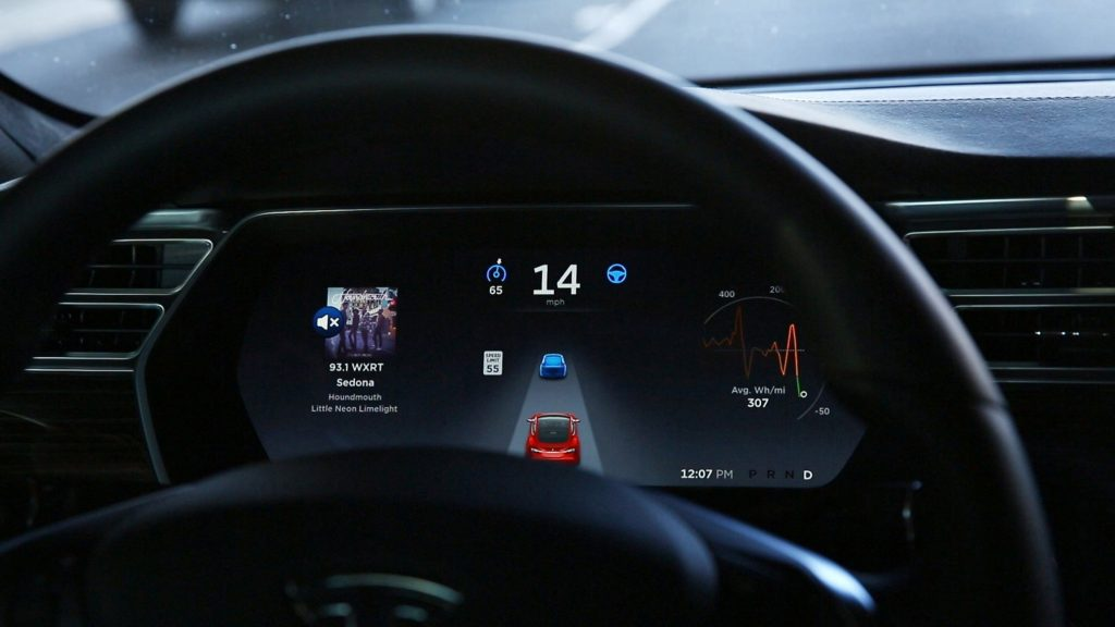 The in-dash display of a Tesla shows Autopilot adaptive cruise software in use