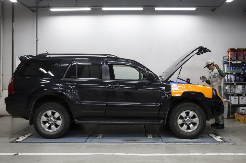 A Japanese technician works on a Toyota SUV
