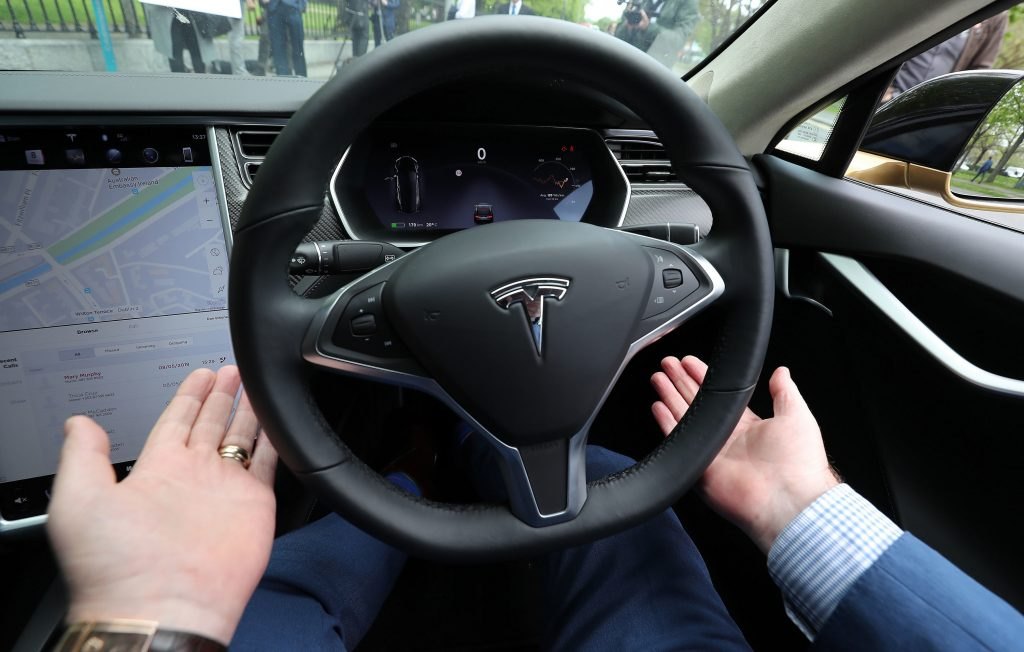 A man rides in a Model S with his hands off the wheel, letting the car drive for him